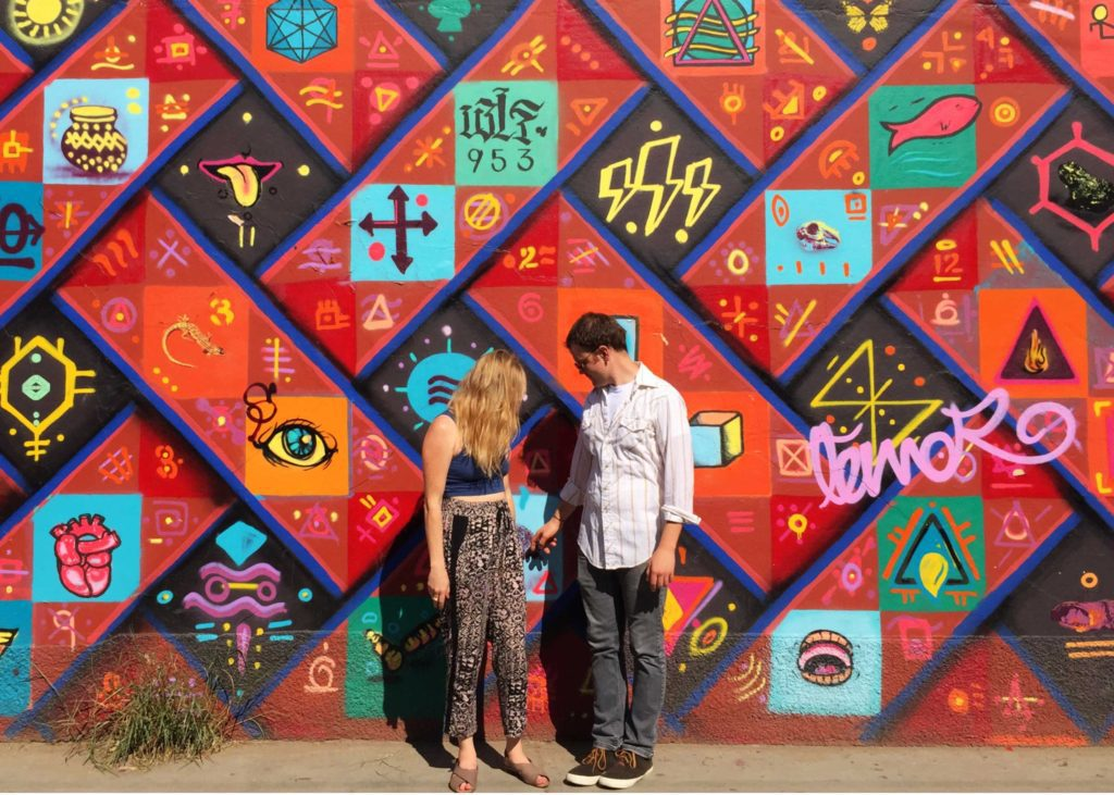 Tara and Thom in front of a mural in Oaxaca, Mexico