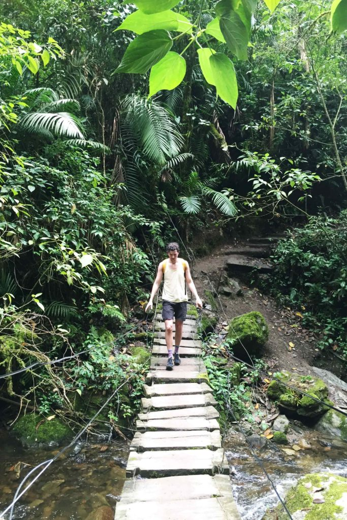 Justin crossing a suspension bridge hiking Valle de Cocora
