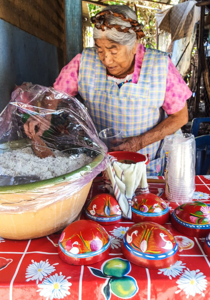 Local woman serving Tejate - the most popular local drink in Oaxaca copy
